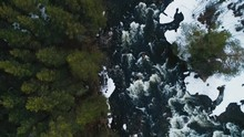 Top Down View Of Fast Moving River With Rapids Surrounded By Winter Forrest In Russian North