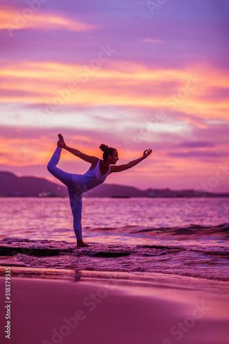 Obraz na plátně Woman practices yoga at seashore