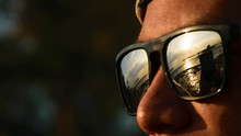 Cropped Image Of Man Wearing Sunglasses With Sea Reflection