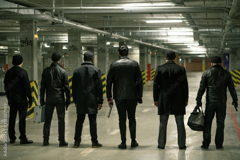Fototapeta Rear view of row of criminals or gangsters in black standing on parking area