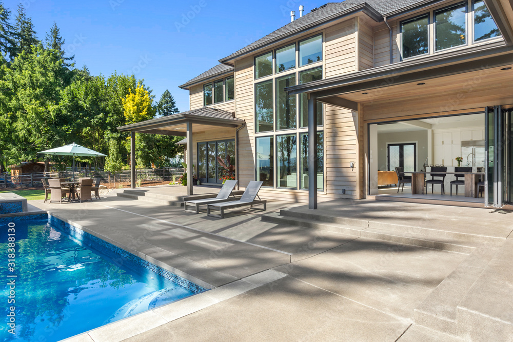 Fototapeta Luxury home exterior and pool on sunny day with blue sky