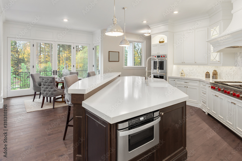 Fototapeta Beautiful kitchen in new luxury home with hardwood floors, white cabinets, and quartz countertops. Shows eating nook.