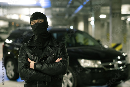 Photo Male criminal in black jacket and balaclava standing on parking area