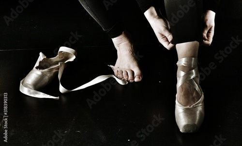 Obraz Low Section Of Female Ballet Dancer Wearing Shoes On Floor - fototapety do salonu