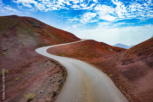fototapeta na szkło Image related to unexplored road journeys and adventures.Road through the scenic landscape to the destination in Timanfaya natural park in Lanzarote,Canary island,Spain