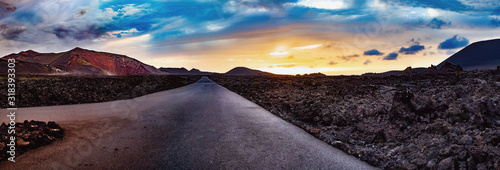 Obraz Image related to unexplored road journeys and adventures.Road through the scenic landscape to the destination in Timanfaya natural park in Lanzarote,Canary island,Spain - fototapety do salonu