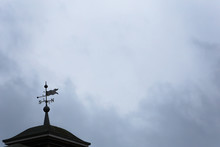 Low Angle View Of Weather Vane On Roof Against Cloudy Sky