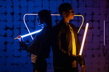 Young Couple With Neon Lamps On Dark Color Background