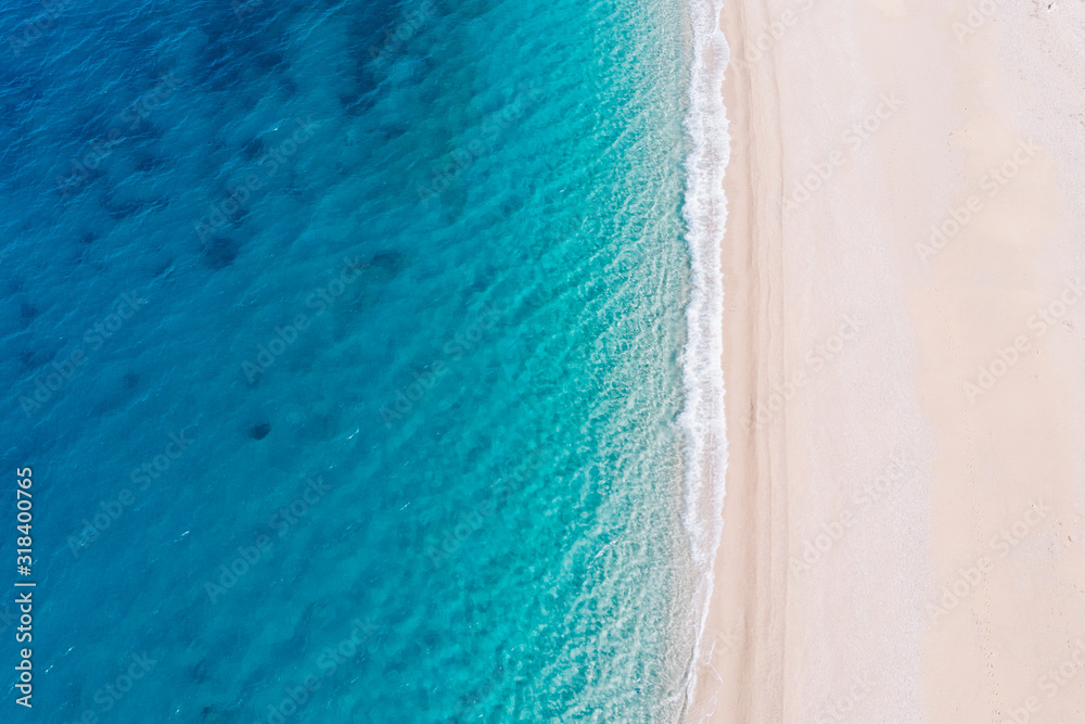 Fototapeta Top-down aerial view of a white sandy beach on the shores of a beautiful turquoise sea.