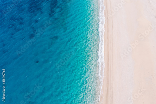 Fototapeta Top-down aerial view of a white sandy beach on the shores of a beautiful turquoise sea. obraz