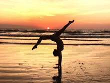 Side View Of Silhouette Girl Practicing Handstand At Beach During Sunset