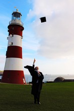 Student Throwing Mortarboard While Standing Against Lighthouse