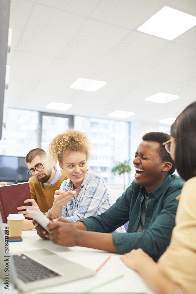 Fototapeta Multi-ethnic group of students studying in college library, focus on African-American man laughing happily, copy space