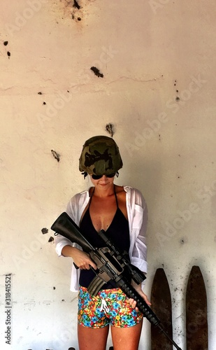 Photo Woman Holding Ak-47 While Standing Against Wall