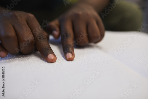 Tablou Canvas Closeup of unrecognizable blind African man reading braille book while studying