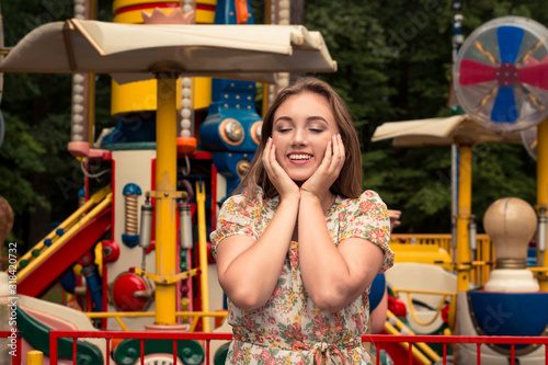 Photo Portrait of a girl in a light dress covering her cheeks with admiration in an amusement park