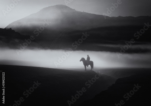 Person Riding Horse On Landscape Against Mountains - fototapety na wymiar