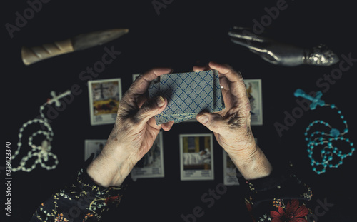 Photo Old woman shuffle tarot cards above other tarot cards