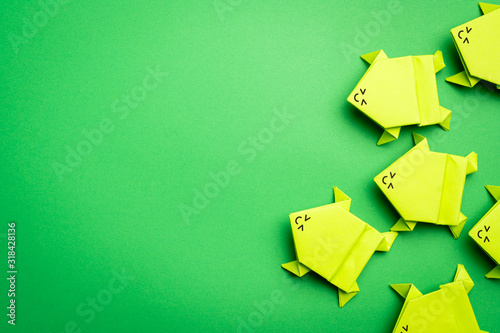 Group of origami green paper frogs isolated on green background Wallpaper Mural