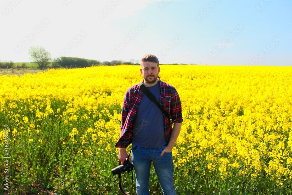 Fototapeta Portrait Of Man Holding Camera While Standing At Rape Field