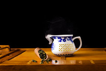 Chinese Tea Ceremony. Ceramic Jug With Green Oolong Tea Tieguanyin With Vapour And Wooden Scoop On A Black Background.
