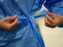 Tying Blue Medical Gown Before...
