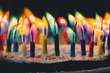 Close-Up Of Colorful Candles Burning On Birthday Cake