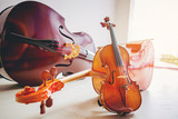 Double bass (Contrabass), cello and violin lying at the floor with composition with bright background