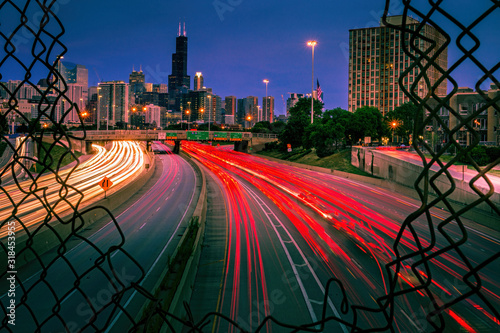Obraz na plátne Long exposure of Chicago highway traffic seen through a fence opening