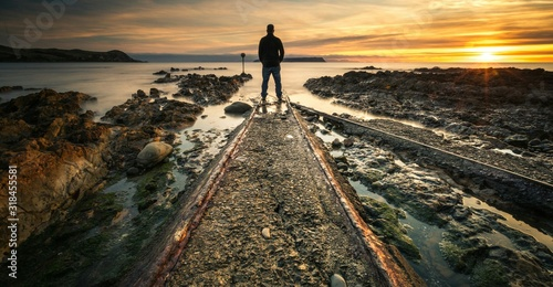 Rear View Of Man Standing On Shore Against Sky During Sunset Fototapeta