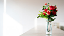 Bouquet Of Red Plastic Roses In A Glass Bottle Placed On A Wooden Table. Wedding Decorations, Valentine's Day, Home Decorations Or Office. Doing Export Business Of Fake Flowers. Copy Space