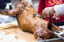 Cutting The Mutton Hulk Fried On A Grill For The Pilaf. Male Hands Keep A Knife In Gloves And Cut Meat