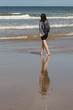 Full Length Of Woman With Backpack Walking On Shore