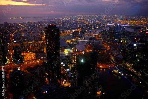 Fototapeta HIGH ANGLE VIEW OF ILLUMINATED CITYSCAPE AGAINST SKY AT NIGHT obraz na płótnie