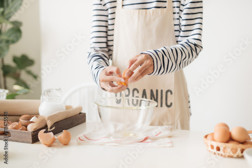 Male hands are breaking an egg into bowl to make dough on white table Canvas Print