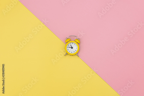 Yellow little alarm clock on pink and yellow background Canvas Print