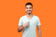 canvas print picture - This is me! Portrait of glad satisfied brunette man with beard in white t-shirt pointing at himself, looking at camera with proud and boastful smile. indoor studio shot isolated on orange background