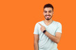 canvas print picture - Look here! Portrait of positive friendly brunette man with beard in casual white t-shirt standing pointing at left, empty space for text, advertise. indoor studio shot isolated on orange background