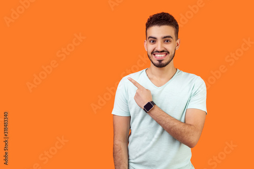 Obraz Look here! Portrait of positive friendly brunette man with beard in casual white t-shirt standing pointing at left, empty space for text, advertise. indoor studio shot isolated on orange background - fototapety do salonu