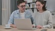 Young Couple reacting to Loss on Laptop in Living Room