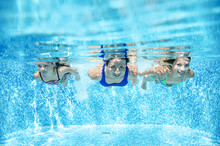Family Swims In Pool Underwater, Happy Active Mother And Children Have Fun Under Water, Fitness And Sport With Kids On Summer Vacation On Resort
