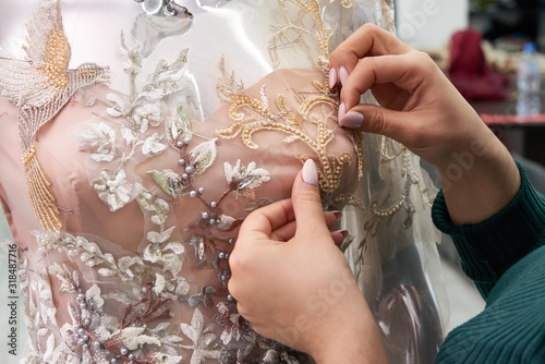Vászonkép Dressmaker fixing white lace wedding dress on a mannequin in tailor studio