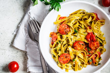 Green Spinach Pasta With Tomatoes And Herbs, Top View. Healthy Vegan Food Concept.