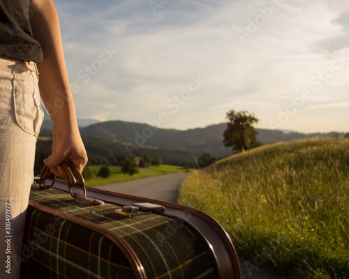 Midsection Of Woman Holding Suitcase On Road Against Sky - fototapety na wymiar