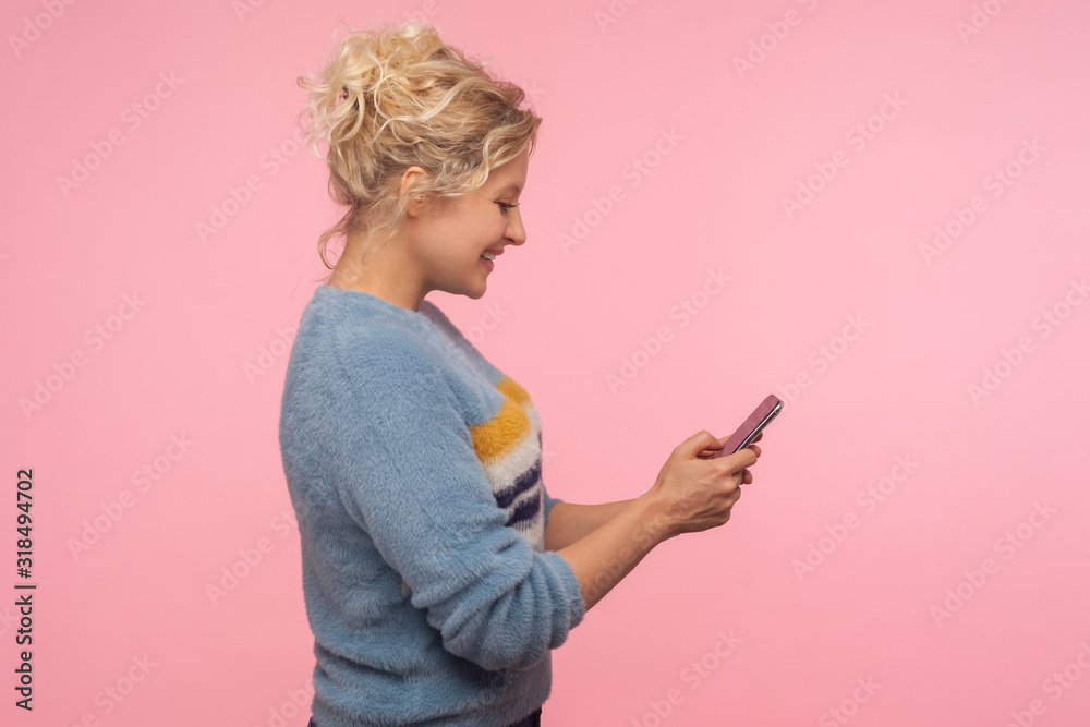 Fototapeta Side view of cheerful cute woman with curly hair in sweater chatting in cellphone, reading pleasant message and smiling charmingly, using mobile phone. indoor studio shot isolated on pink background