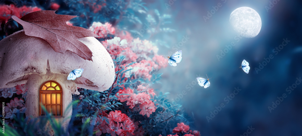 Fototapeta Magical fantasy elf or gnome mushroom house with window in enchanted fairy tale forest, fabulous blooming rose flower garden, flying butterflies on mysterious blue background, shine moon ray in night
