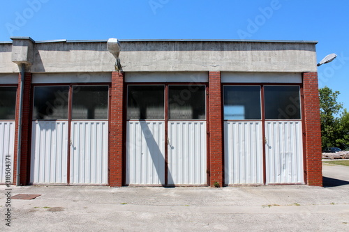 Fotografia Row of old garages with tall metal doors divided with red brick walls and large