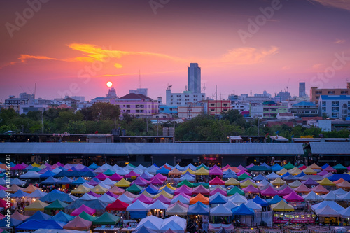 Photo MULTI COLORED CITYSCAPE BY RIVER AGAINST SKY DURING SUNSET
