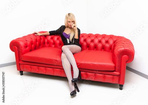Obraz na plátně una giovane donna con lunghi capelli biondi è seduta sul divano rosso e sta pens
