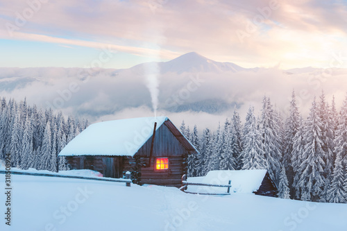 Fotografie, Tablou Fantastic winter landscape with wooden house in snowy mountains